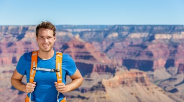 Grand Canyon hiker man portrait with backpack bag. Hiking male tourist on Grand Canyon, Arizona, USA. Hiking athlete enjoying view of nature landscape wearing backpack. Young man relaxing after hike.