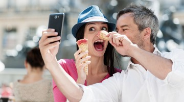 couple taking a selfie while eating an ice cream on a terrace