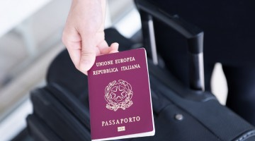 Hand holding Italy passport, ready to travel